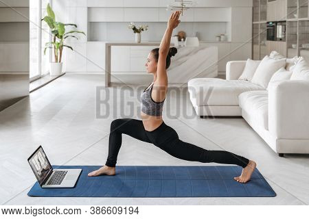 Beautiful Young Woman In Sports Clothing Practicing Yoga At Home, Watching Online Tutorial, Repeatin