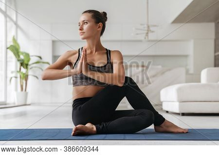Young Happy Fit Female Athlete In Sportswear Practicing Yoga On Exercise Mat At Home In Her Living R