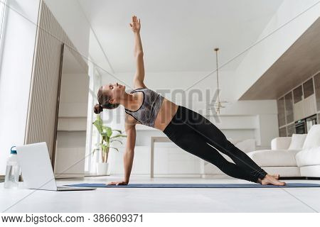 Pretty Girl Wearing Leggings And Short Top Standing In Side Plank On One Hand At Home, Training Body