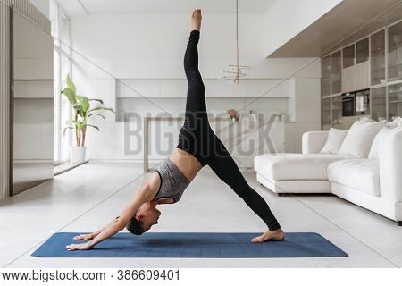 Young Balanced Woman In Sportswear Doing One Legged Dolphin Yoga Pose On Mat At Home In Her Living R