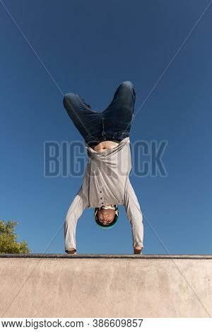 A Young Male Roller Skater In A Helmet Does A Dangerous And Daring Trick On A Ramp In A Skate Park O