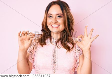 Young beautiful caucasian woman holding macaron doing ok sign with fingers, smiling friendly gesturing excellent symbol