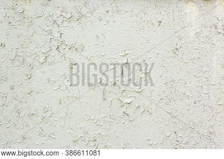 Old Weathered Painted White Plastered Peeled Wall Background. Cracked Flaked Shabby Wall With Rundow