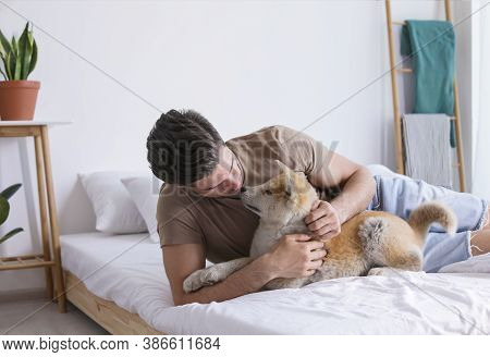 Happy Man With His Cute Akita Inu Puppy At Home