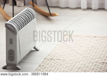 Modern Electric Heater In Stylish Room Interior. Space For Text