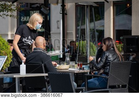 Vilnius, Lithuania - September 20 2020: Blonde Hair Nice Waitress With A Mask Serving At The Table A