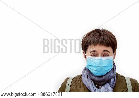 Young Brunette Woman Laughing With Disposable Blue Medical Mask On Fase. Laughter Conquers Disease.