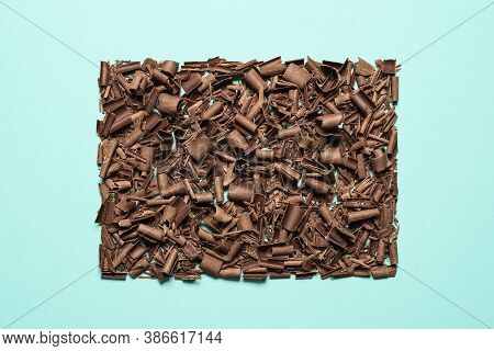 Chocolate Pieces And Curls Isolated On A Seamless Blue Background. Flat Lay Of Grated Chocolate Symm