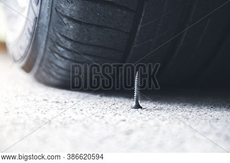 Close Up Of Sharp Metal Screw On Road Nearly To Puncture A Car Tire