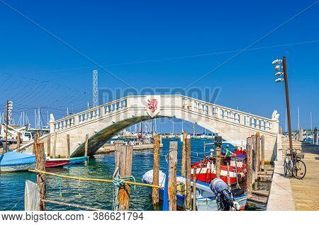 Stone Bridge Ponte Di Vigo Across Vena Water Canal With Colorful Boats Near Pier Embankment In Histo
