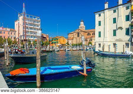 Chioggia, Italy, September 16, 2019: Colorful Boats Moored On Pier In Port Marina And Cathedral Sant