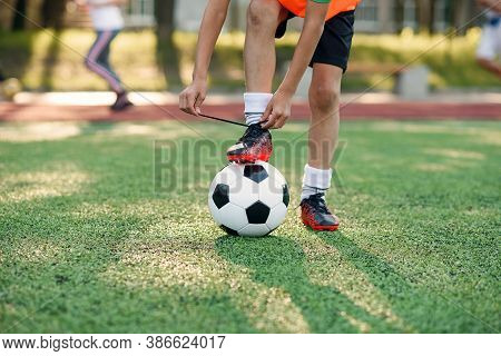 Close Up Soccer Boot Of Football Player Which Puts His Leg On Ball And Tying Shoelace On Artificial