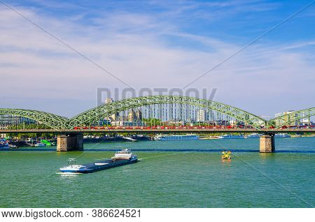 The Hohenzollern Bridge Or Hohenzollernbrucke Across Rhine River With Cargo Ships Sailing On Water,