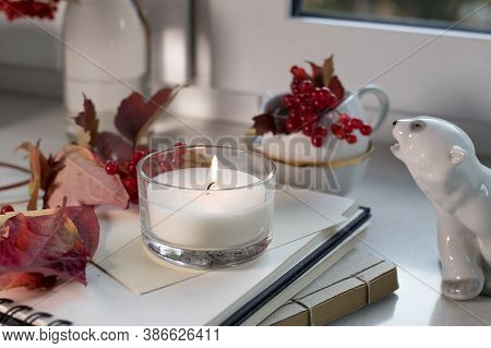 A Porcelain Figurine Of A Polar Bear With A Viburnum Branch In The Cup On The Windowsill. Photo For