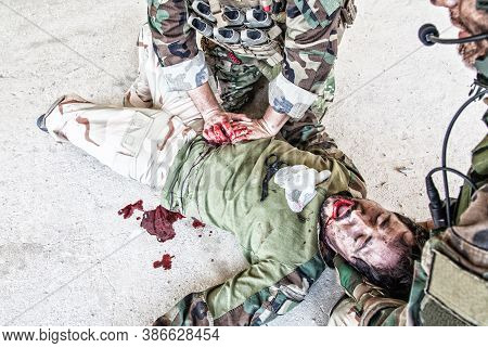 Soldiers Trying To Stop Bleeding At Wounded Comrade Who Lying On Floor, Suffering And Screaming In P