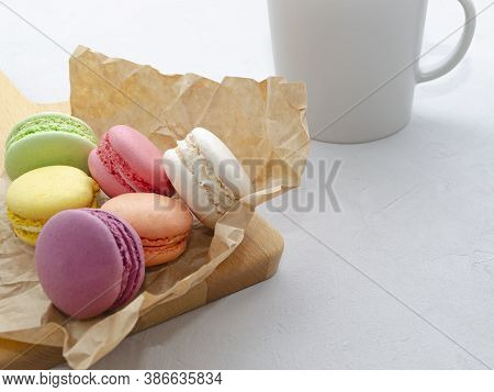 Multicolored Appetizing Crispy Macarons On Baking Paper On A Light Gray Background With A Cup Of Cof