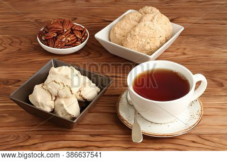 Meringue Cookies With Hazelnuts, Almond Cookies In A Square Bowl And Pecan Nuts In A Small Bowl, And