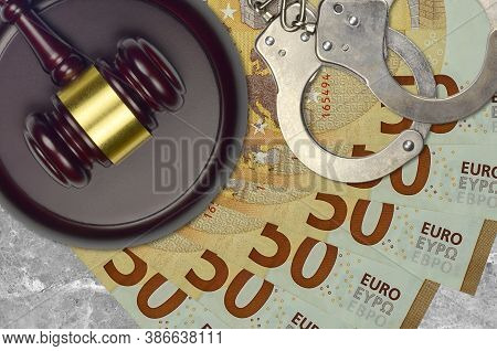 50 Euro Bills And Judge Hammer With Police Handcuffs On Court Desk. Concept Of Judicial Trial Or Bri