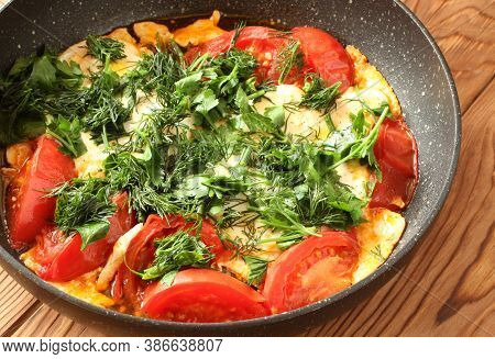 Scrambled Eggs With Tomatoes, Sprinkled With Chopped Dill And Parsley In A Black Skillet On A Brown