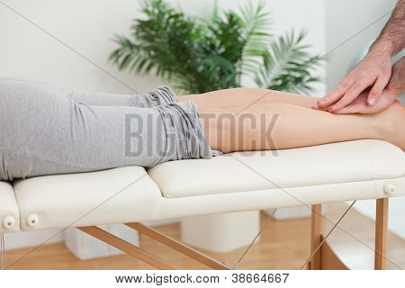 Physiotherapist massaging the legs of a woman in a physio room