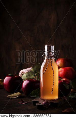 Apple Vinegar. Bottle Of Apple Organic Vinegar Made From Fermented Apples On Wooden Background. Heal