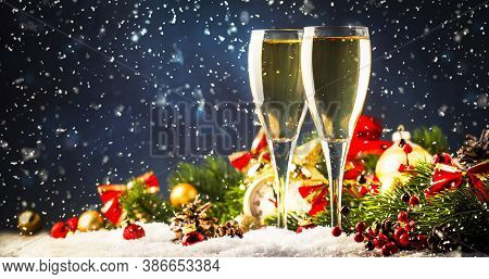 Two Champagne Glasses And Christmas Decoration Over Blue Snow Golden Bokeh Background. Happy New Yea