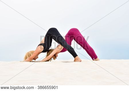 Two Beautiful Young Women Performing Yoga Pose Adho Mukha Svanasana Together On The Beach