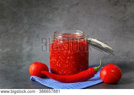 Ground Hot Red Pepper With Tomatoes In A Glass Jar On A Dark Background. A Spicy Seasoning Made From