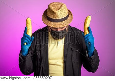 A Man In A Mask And A Hat Holds Bananas In Both Hands As A Weapon. Irony About Carrying Arms