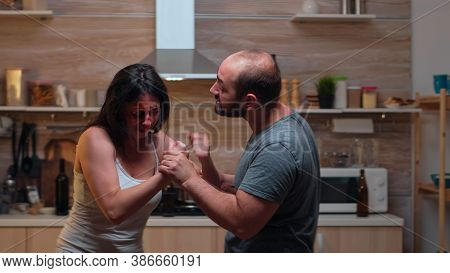Drunk Partner Abusing Woman In The Kitchen. Abused Terrified Beaten Wife Covered In Bruises Sufferin