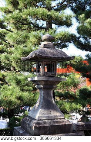 Stone Lantern Of Japanese Style And Pine Tree Background In Fushimi Inari Taisha Shinto Shrine. The