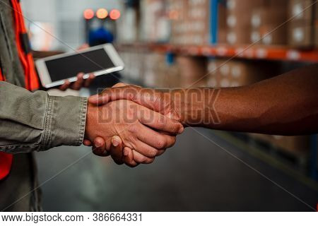 Close Up Of Caucasian An Ethnic Male Co-workers Shaking Hands After Making Successful Deal In Wareho