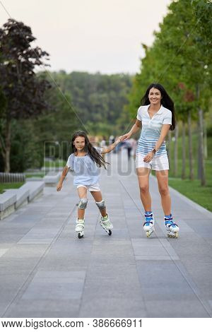 Young Mother And Daughter Rollerskating In Summer Park. Happy Family Have Fun Outdoor