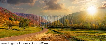 Road Winding Through The Country Valley At Sunset. Wonderful Autumn Landscape In Mountains In Evenin