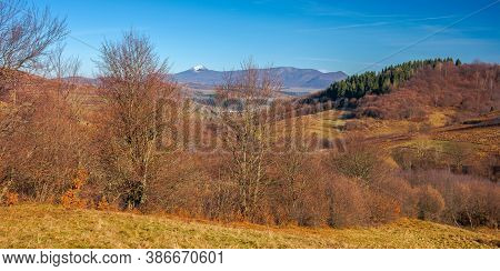 Mountainous Countryside In November. Leafless Trees On Hills Rolling In To The Rural Valley. Snow Ca