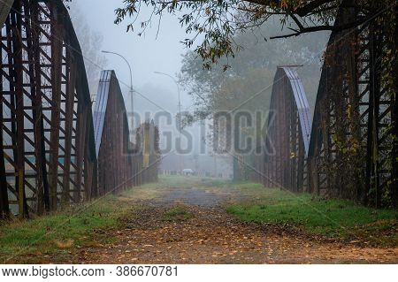 Abandoned Metal Bridge In Morning Fog. Dangerous Construction In Autumnal Countryside Scenery At Sun