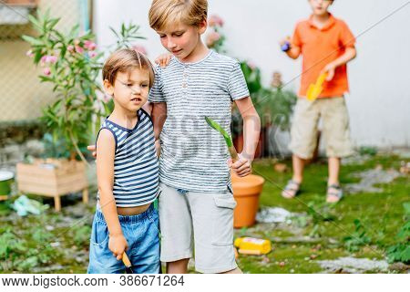Two Children Boy Working At Backyard. Brother With Gardening Tools Spending Time, Playing, Create A