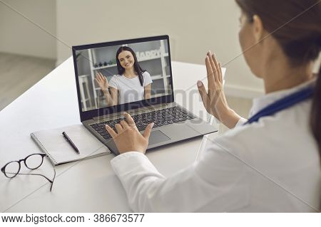 Woman Patient Greeting Her Doctor Online From Laptop Screen During Videocall On Laptop
