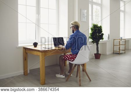 Online Work At Home. A Young Man In Typing In A Laptop Sitting At A Table At Home. Remote Work.