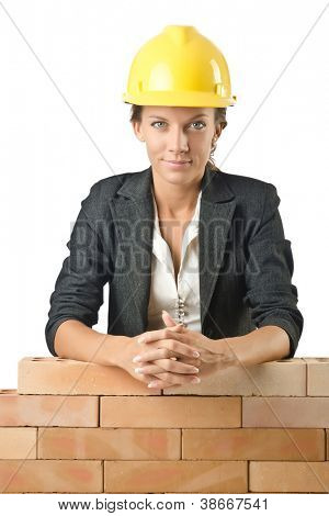 Young female builder near brick wall
