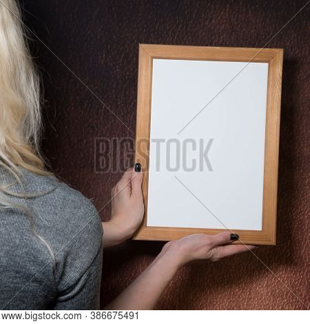 Partial View Of Young Woman Holding Wooden Frame, Brown Background, Mock-up, Empty Space.