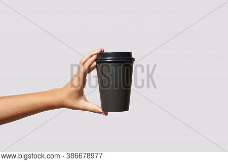 Girl Hand Hold Coffee Plastic Cup. Grey Background With Copyspace. Female Arm Holding Paper Glass. T