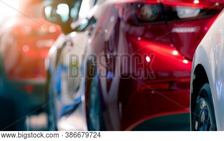 Blurred Red And White Car Parked In A Row. Automotive Industry. Electric Vehicle Global Market Conce