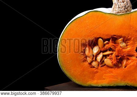 Pumpkin With Orange Flesh On The Wooden Board Against The Black Background