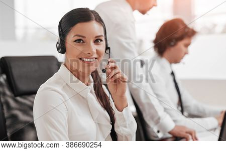 Positive Young Female Employee In White Blouse With Headset Consulting Customers While Working In Ca