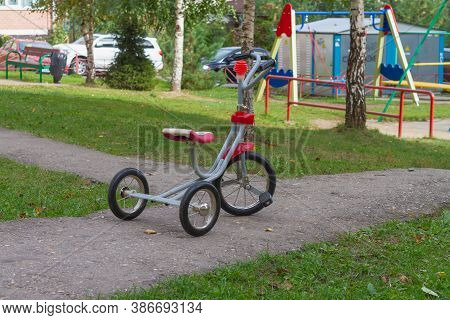 Red Tricycle On The Playground In Summer.
