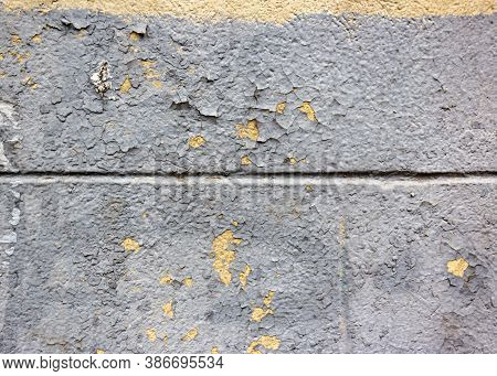 Cracked Peeled White Paint With Yellow Spots On An Old Stone Wall. Old Weathered Painted White Plast