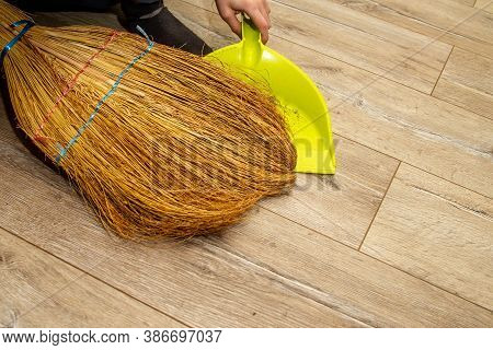 Sweep The Floor With A Broom In The Apartment. Manual Cleaning Of The Floor In The House. Help With