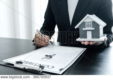 The Hand Of The Real Estate Agent, Holding A Pen And Drafting An Agreement On The Home Insurance Con