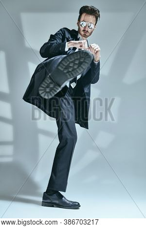 Modern stylish man in elegant black suit, white shirt and sunglasses posing  in motion on a grey background with shadows. Full length portrait of a modern businessman. Men's fashion.